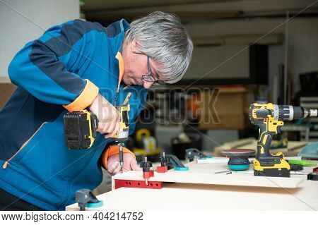 Caucasian Man Makes His Own Home Furniture As A Hobby In His Garage.relax Time And Hobbies Concept