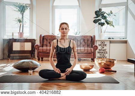 Peaceful And Warm Living Room With Styled Furniture And Caucasian Woman Relaxes Doing Yoga Sitting O