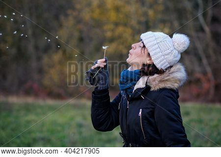 Young woman blowing a dandelion in the wind near a forest
