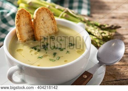 Fresh Green Asparagus Soup In Bowl On Wooden Table