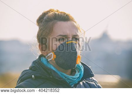 Woman wearing a real anti-pollution, anti-smog and viruses face mask; dense smog in air.