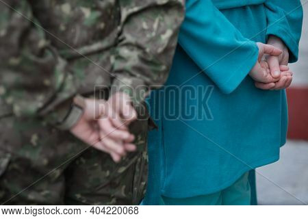 Shallow Depth Of Field (selective Focus) Image With The Hands Of A Medic And The Ones Of A Military