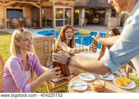 Group Of Young Friends Having A Poolside Barbecue Party, Drinking Beer And Having Fun Spending Sunny