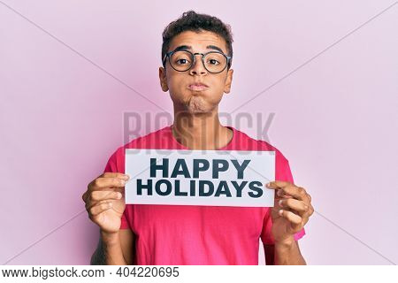 Young handsome african american man holding happy holidays message puffing cheeks with funny face. mouth inflated with air, catching air.