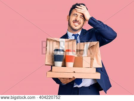 Young hispanic man wearing suit holding takeaway coffee and food stressed and frustrated with hand on head, surprised and angry face