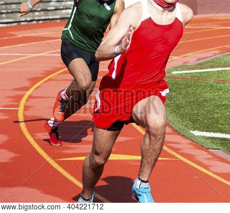 Two High School Boys Competing In A Sprint Race On An Outdoor Track.