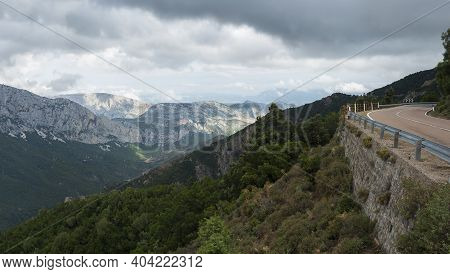 Panoramic View Of Landscape Of Supramonte Mountains With Winding Asphalt Road, Green Hills, Trees An