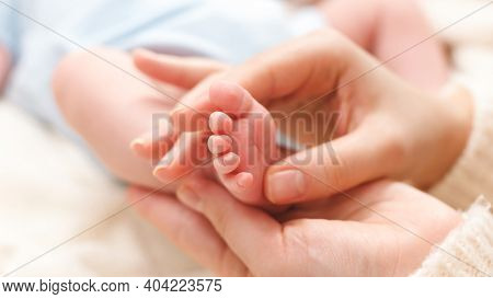 Closeup Image Of Mother Massaging Little Feet Of Her Newborn Baby Boy Lying On Bed