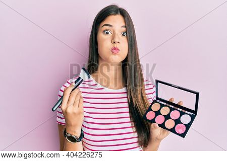 Young brunette woman holding makeup brush and blush palette puffing cheeks with funny face. mouth inflated with air, catching air.
