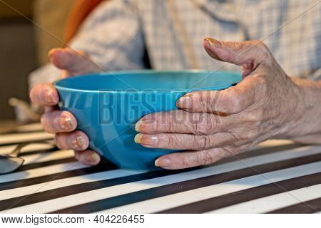 Elderly Woman Holding A Bowl Of Soup.