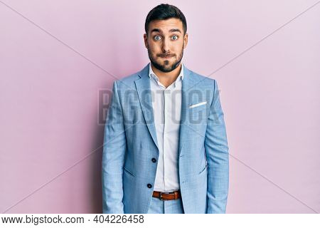 Young hispanic businessman wearing business jacket puffing cheeks with funny face. mouth inflated with air, crazy expression.