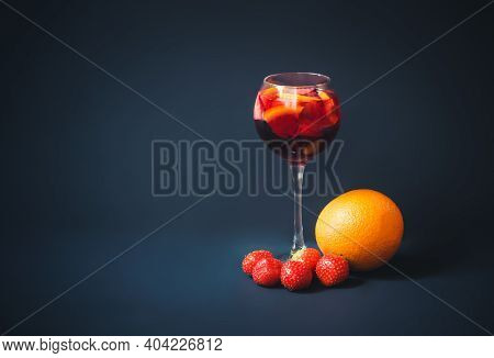 Red Wine Sangria With Orange And Strawberry In Glass, Orange And Strawberry Near. Dark Background. V