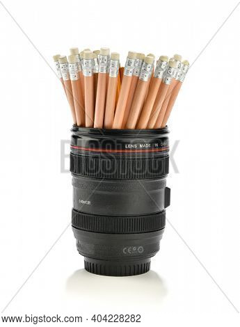 Camera lens pen holder with pencils isolated on white background
