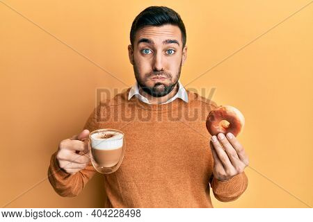 Young hispanic man eating doughnut and drinking coffee puffing cheeks with funny face. mouth inflated with air, catching air.