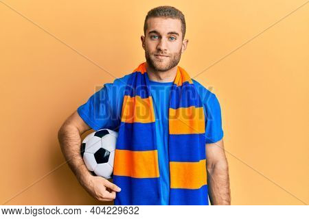 Young caucasian man football hooligan cheering game holding ball thinking attitude and sober expression looking self confident