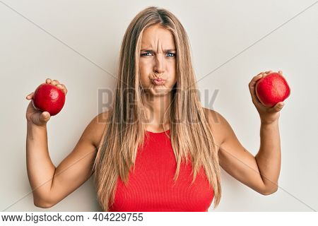 Young blonde woman holding red apples puffing cheeks with funny face. mouth inflated with air, catching air.