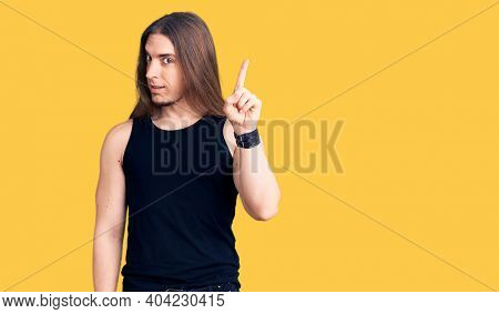 Young adult man with long hair wearing goth style with black clothes pointing finger up with successful idea. exited and happy. number one.