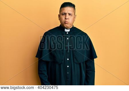 Young latin priest man standing over yellow background puffing cheeks with funny face. mouth inflated with air, crazy expression.