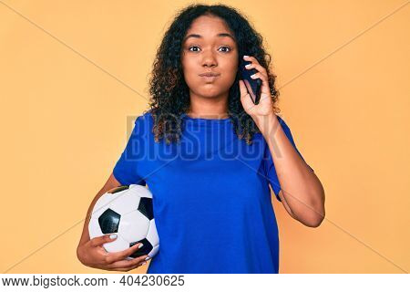 Young african american woman holding football ball talking on the smartphone puffing cheeks with funny face. mouth inflated with air, catching air.