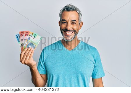 Middle age grey-haired man holding australian dollars looking positive and happy standing and smiling with a confident smile showing teeth