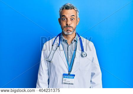Middle age grey-haired man wearing doctor uniform and stethoscope puffing cheeks with funny face. mouth inflated with air, crazy expression.