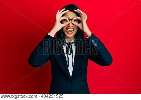 Beautiful asian young woman wearing business suit doing ok gesture like binoculars sticking tongue out, eyes looking through fingers. crazy expression.