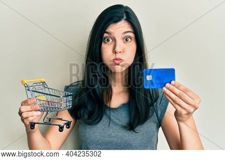 Young hispanic woman holding small supermarket shopping cart and credit card puffing cheeks with funny face. mouth inflated with air, catching air.