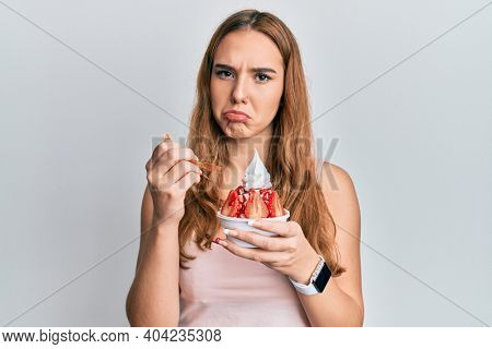 Young blonde woman eating strawberry ice cream depressed and worry for distress, crying angry and afraid. sad expression.