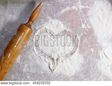 A Heart Is Drawn On The Flour Scattered On The Table, And A Rolling Pin For Rolling Out The Dough Li