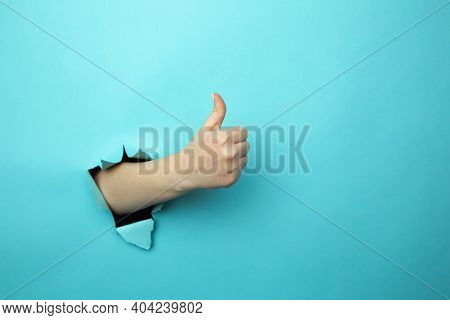 Woman Shows Like Gesture Through Torn Blue Wall, Keeps Thumb Up, Says You Are Best, Demonstrates App