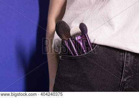 Makeup Brushes Sticking Out Of Black Jeans Pocket On Colorful Blue Background. Professional Makeup A