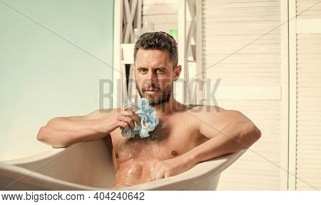 Sex And Relaxation Concept. Macho Attractive Nude Guy. Sexy Man In Bathroom. Wash Off Foam With Wate