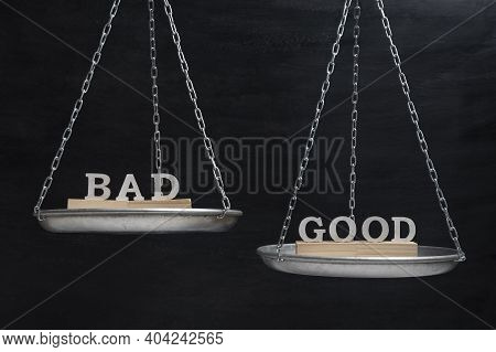 Words Bad And Good In Balance. Scales On Black Background Close Up.