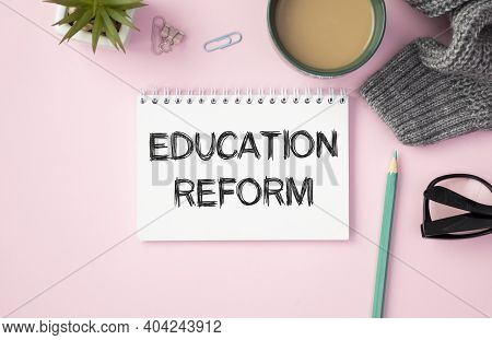 Notepad With The Inscription Education Reform, A Cup Of Coffee, Glasses And A Pencil On A Pink Backg