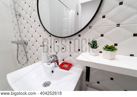 Modern White And Black Toilet Interior. White Sink With Water Tap And Toiletries, Above It Large Rou