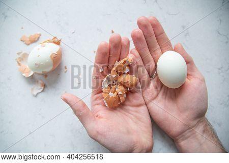 Male Hands Peeling A Boiled Egg Shell.