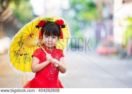 Girl Wearing Red Cheongsam Walks Yellow Vintage Umbrella, A Sweet Smile. Child Looking At Camera. Ch
