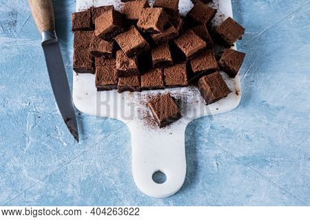Chocolate ganache truffle squares dusted with cacao being cut into cubes