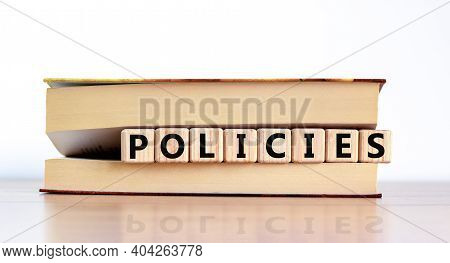 Policies Symbol. Concept Word 'policies' On Wooden Cubes Between Pages Of A Book On A Beautiful Wood