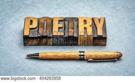 poetry word abstract - text in vintage  letterpress wood type with a stylish pen against textured paper