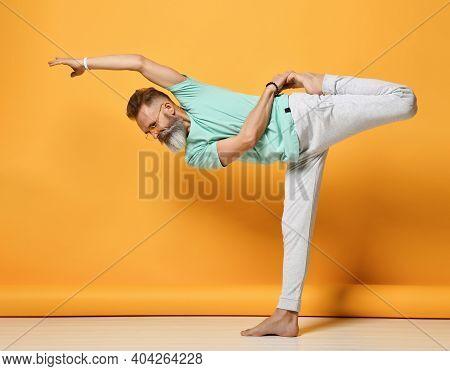 Mature Handsome Gray-haired Brutal Man In Fashionable Sportswear, Practicing Natarajasana, The Maste