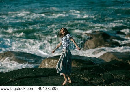 A woman dancer is engaged in choreography on the Atlantic coast.