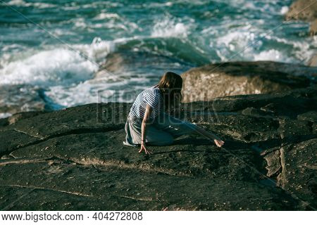 A woman dancer is engaged in choreography on the ocean coast.