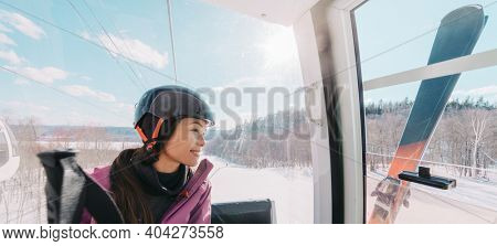 Winter sport Asian woman sitting in ski lift going up the hill at ski resort going skiing down the slopes. Banner panoramic of skier wearing helmet with skis.
