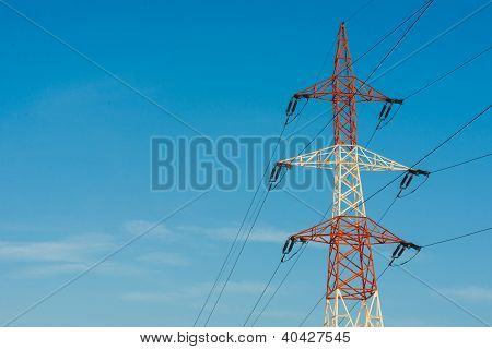 Colorful electricity pillar against blue sky. High voltage power line