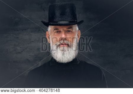 Bearded Grandfather Dressed In Old Fashioned Clothing With Top Hat Poses In Dark Background.