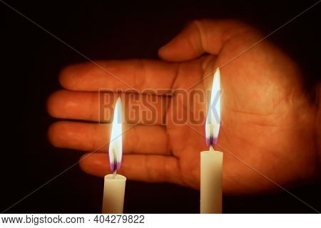 Someone\'s Hand Covering The Candle In A Dark Design For The Background, The Candle In The Dark Symb