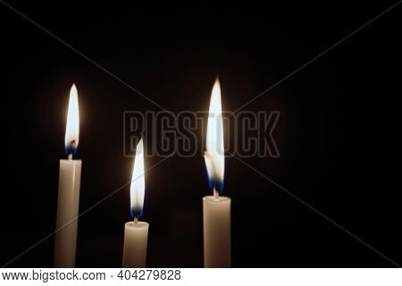 White Candles Burning In The Dark With Lights Glow. The Burning Candle's Flame In The Dark Backgroun