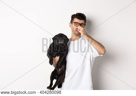 Young Man Shut Nose As Holding Pug, Disgusted With Bad Smell Fart Of Animal, Standing Over White Bac