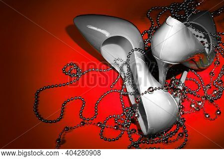Beautiful Patent Leather White Shiny Female Stilettos And Beads On A Red